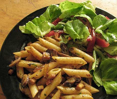 Gebratene Nudeln mit Tofu, Pilzen, Zwiebeln und Salat.